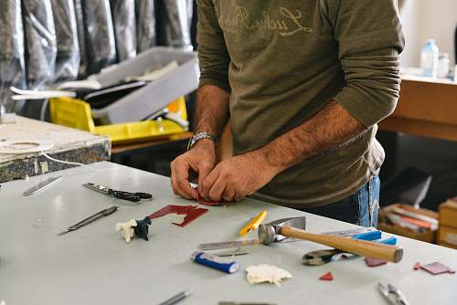 person man holding tool in front of table work