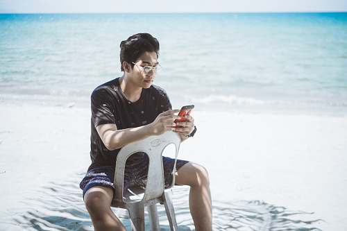 human man in black shirt and blue board shorts sitting on plastic chair near seashore person