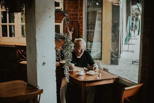 human man in black shirt sits inside restaurant with coffee on front person