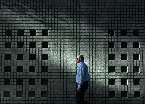 human man in blue dress shirt walking near gray concrete wall person