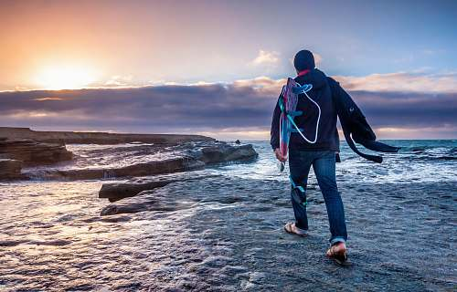 human man in blue jeans walking on gray soil ocean