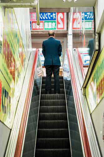 person man in blue suit jacket standing on escalator human