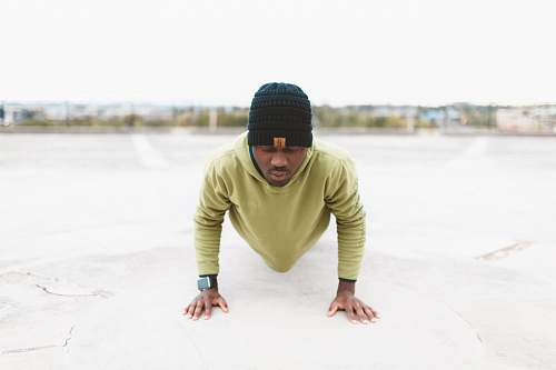 person man in green long-sleeved shirt doing a push-up on gray concrete pavement human