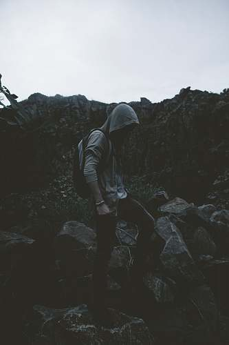 human man in hoodie stepping on rocks person