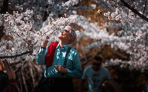 human man in teal dress shirt smelling white flower blossom