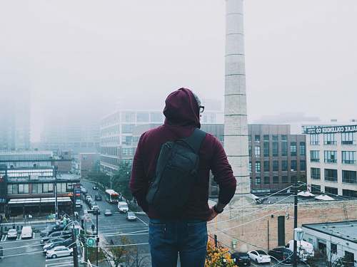 person man looking down the city covered with fogs during daytime human