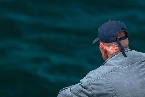 human man looking on body of water wearing black cap person