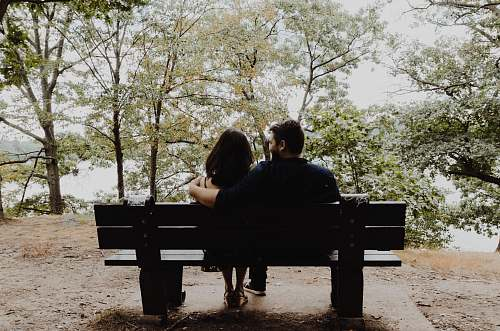 human man looking to woman sitting on black wooden bench in front of tall trees during daytime bench