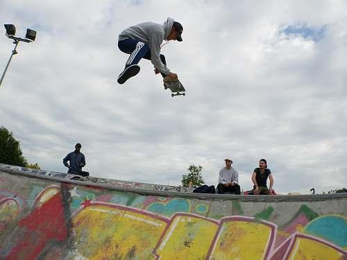 human man on air playing skateboard above skateboard ramp at daytime person