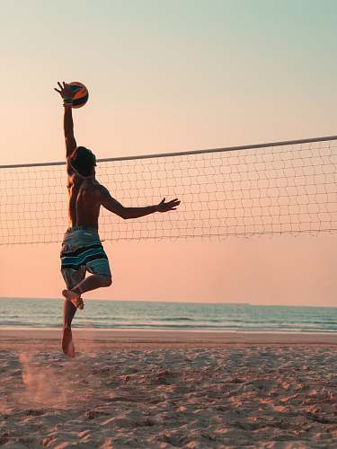 human man playing beach volleyball during daytime person