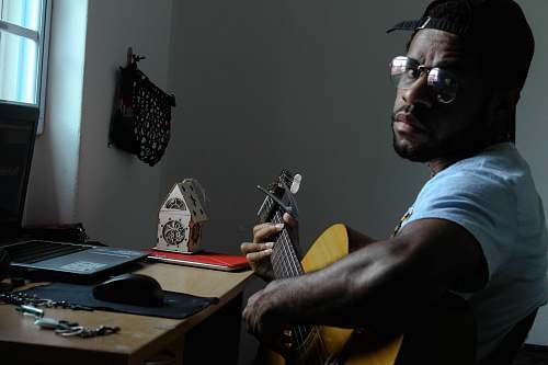 human man playing guitar beside table person