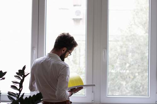 human man reading book in front of window person