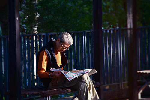 human man reading newspaper while sitting on bench in front of wooden fence person