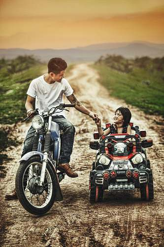 person man riding motorcycle and toddler on a toy car in a road during daytime vehicle
