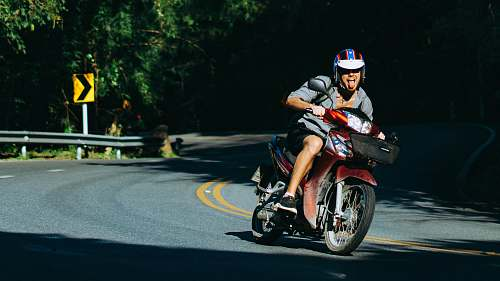 human man riding motorcycle on curved road motorcycle