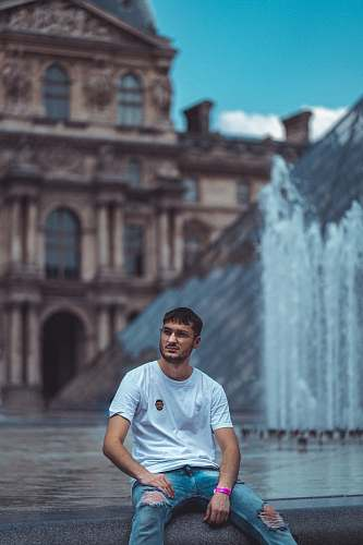 person man sitting beside fountain human