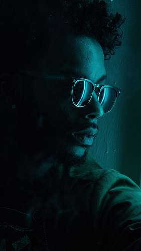 person man sitting near wall wearing black framed sunglasses human
