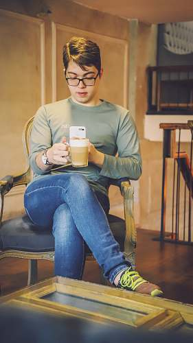 human man sitting on brown armchair while taking photo of a cup person