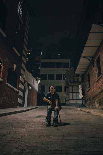 human man sitting on chair between brown brick buildings person