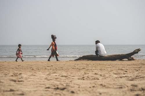 beach man sitting on drift wood ocean