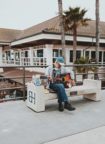 guitar man sitting on outdoor bench playing guitar during daytime musician
