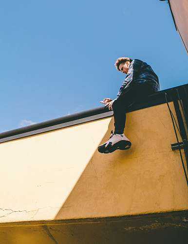 human man sitting on roof under blue sky person