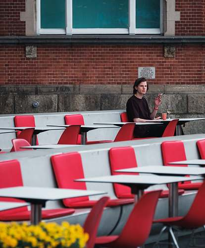 person man smoking cigarette while sitting on red chair brick