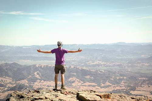 human man stand on brown mountain under blue sky person