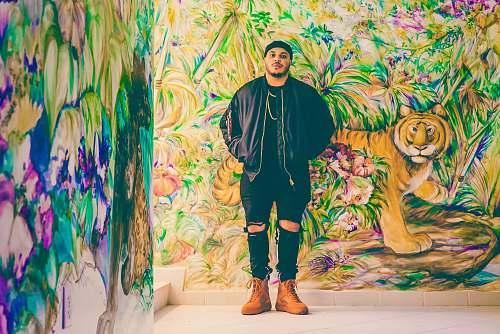 human man standing behind assorted-design graffiti person