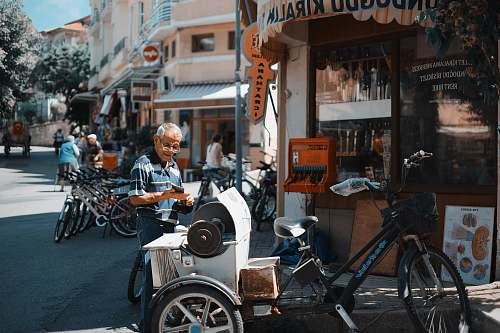 bike man standing behind the trile bicycle