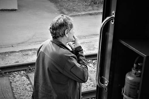 human man standing beside door black-and-white