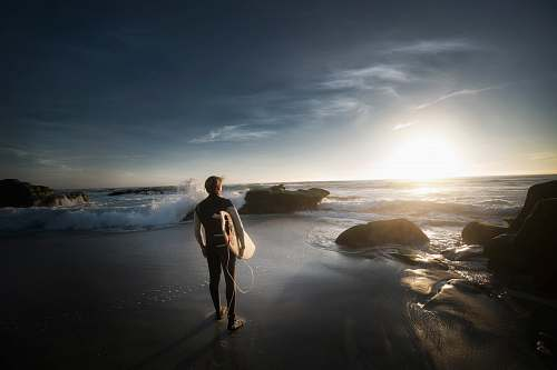 person man standing carrying surfboard near seashore during daytime sand