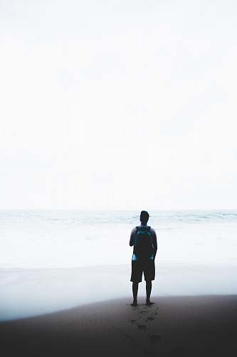 person man standing in front of body of water while carrying blue and black backpack human