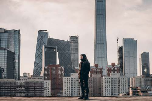 human man standing in front of tall buildings person