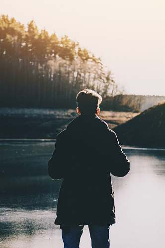 human man standing infront of lake and trees during daytime person