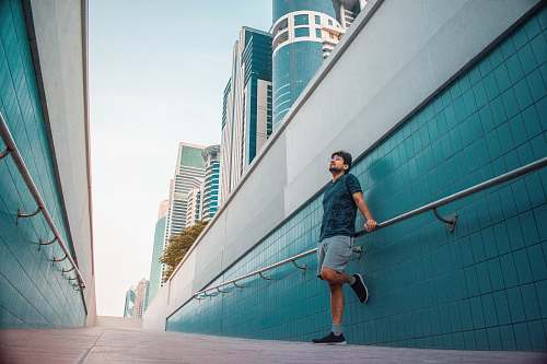 human man standing near blue wall during dayutime person