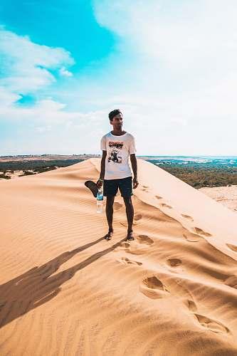 human man standing on desert mountain sand