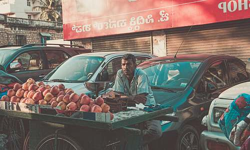 car man vending apples near parked cars during daytime vehicle