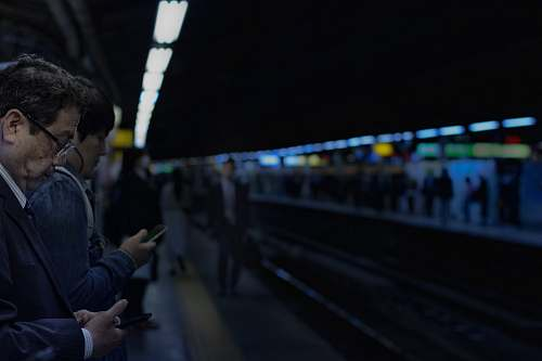 human man waiting for train white holding cellphone person