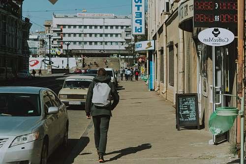human man walking along sidewalk during daytime person