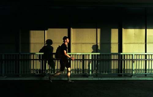 human man walking beside gray metal fence person