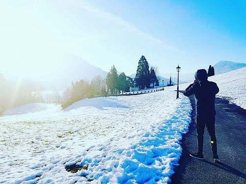 human man walking on path beside snow person