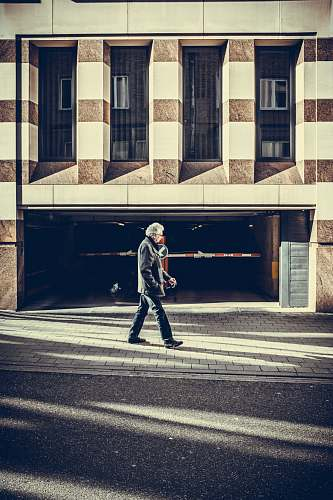 person man walking on pavement in front of concrete structure human