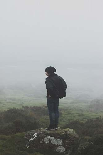 human man wearing black jacket standing on rock person