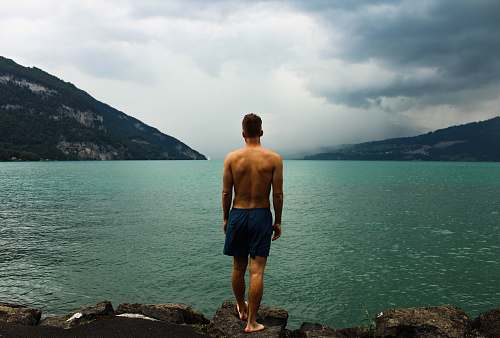 person man wearing black shorts standing in front of body of water switzerland