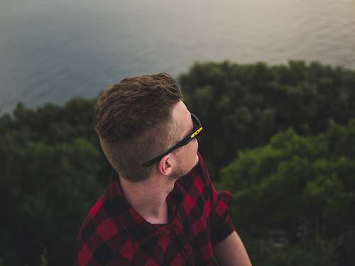 human man wearing black sports sunglasses facing body of water person