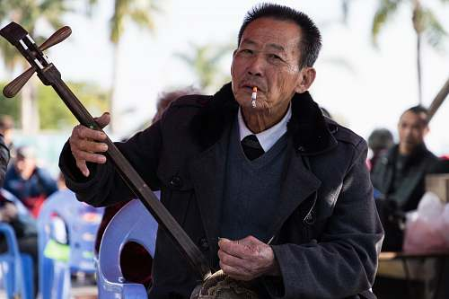 person man wearing black suit holding guitar while smoking human