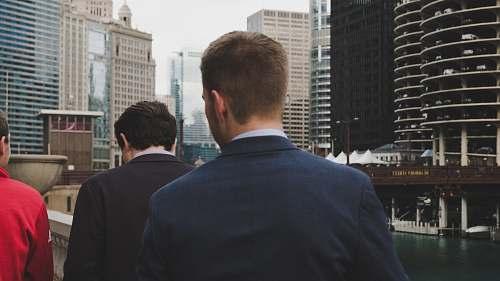 human man wearing blue blazer standing behind two men during daaytime person