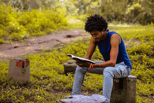 human man wearing blue shirt sitting on the bench reading book person