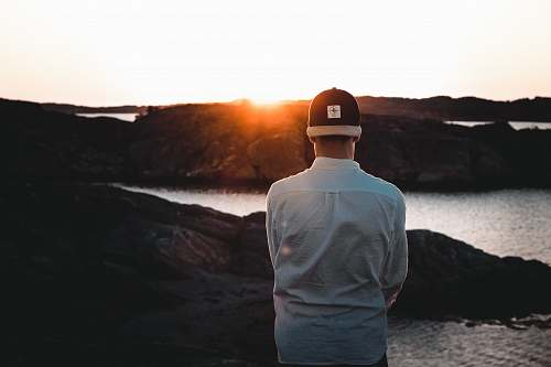 human man wearing cap backwards facing the sea person